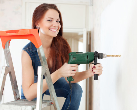 Happy woman drills hole in the wall with drill  at home photo