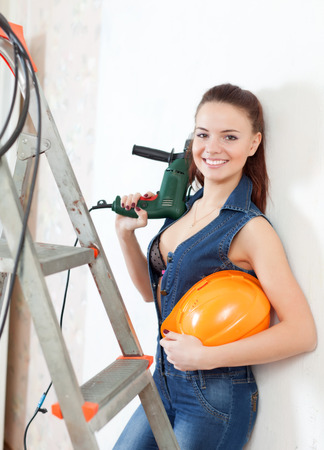 Happy sexy  girl in headphones with drill and hardhat on stepladder photo
