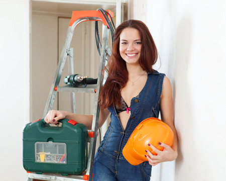Sexy beauty woman with hardhat near staircase in interior photo
