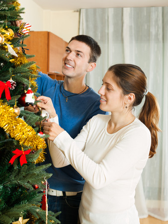 home decorating: Smiling couple decorating Christmas tree in home interior Stock Photo