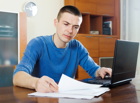 parsimony: serious guy staring financial documents at table in home interior