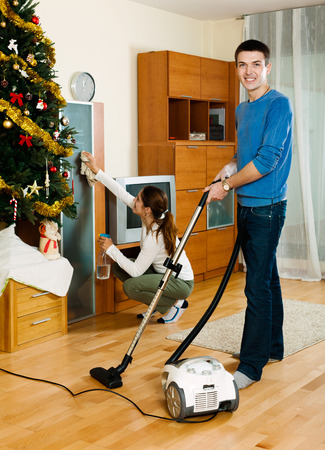 Young adult woman and man doing housework together in home photo