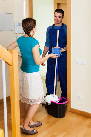houseman: Woman meeting cleaner at the door at home Stock Photo