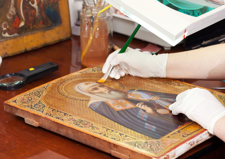 restorer works on ancient icon with brush at restoration workshop photo