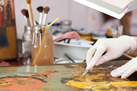 Restorer working on the ancient Christian icon at restoration workshop photo