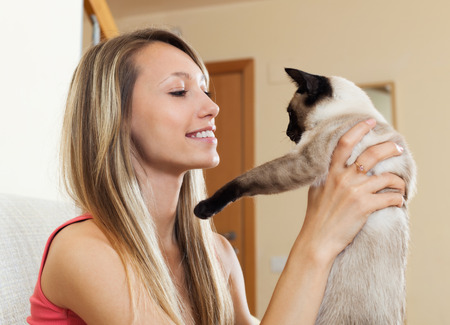 Portrait of young woman sitting on sofa with her cat at home photo