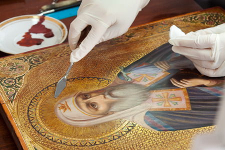restoration of old gilded icon with  filling knife at workshop photo