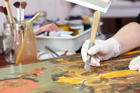 restoration of ancient Christian icon with agate burnisher at  workshop photo