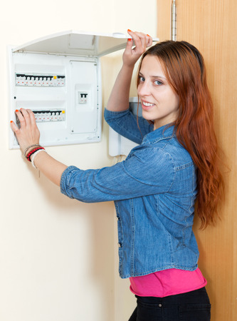 Smiling woman turning off the light-switch at home  photo