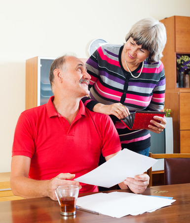Positive mature couple looking financial documents in home   photo