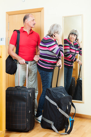 mature  couple with luggage looking in mirror near door in home photo