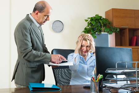 unprofessional: Office scene with angry chief and careless secretary  Stock Photo