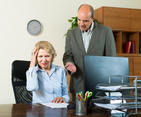 Furious boss screaming at his mature assistant  photo