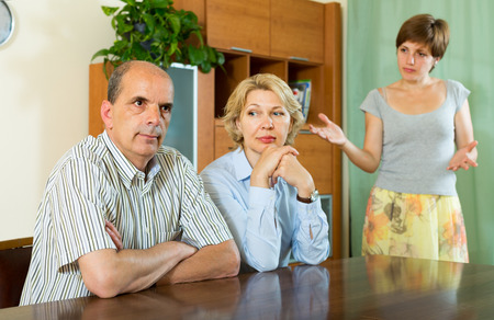 Adult daughter having serious talking with mature parents at home  photo