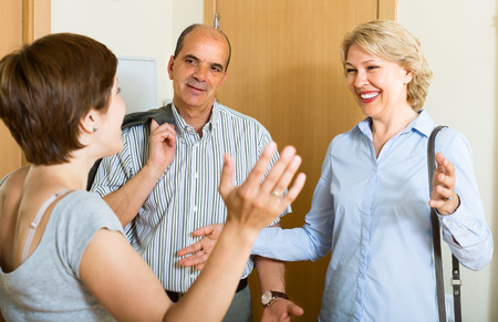 Happy senior family couple visiting adult daughter at home photo