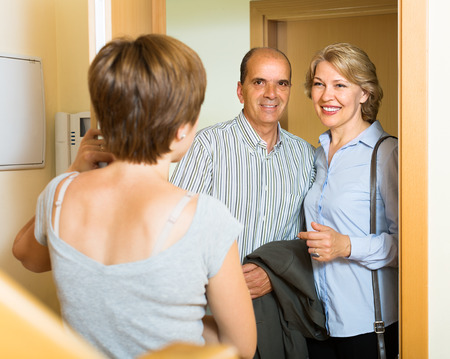 neighbors: Smiling mature family couple visiting daughter at home Stock Photo