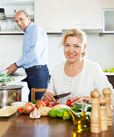 spaniard: happy ordinary mature couple cooking food with vegetables