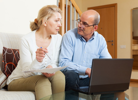 spaniard: Woman reading finance documents with husband in home interior