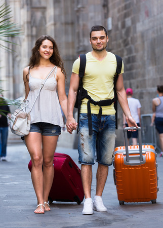 Couple in casual clothes with trunk and backpack outdoor photo