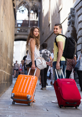 Smiling travelers couple with baggage heading to hotel on foot  photo