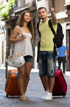 Positive couple of travelers with baggage heading to hotel on foot  photo