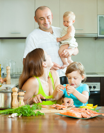20 23 years: Happy family of four fish salmon cooking delicious food in home kitchen
