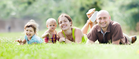 Happy family of four enjoying time at grass in summer park photo