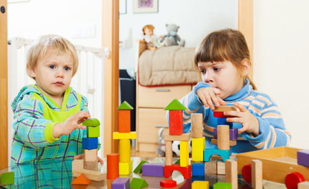 wooden blocks:  serious children playing with wooden blocks