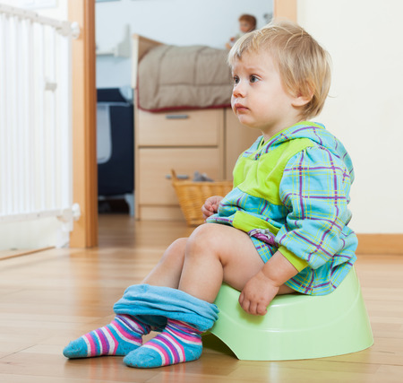 poo: Baby girl sitting on green potty in home interior Stock Photo