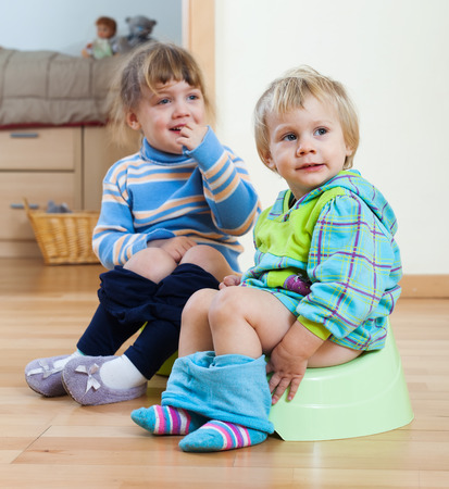 Two children sitting on bedpans in home interior photo