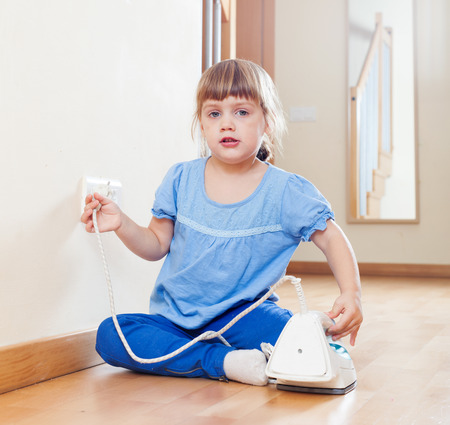 riskiness: three year old child playing with electric iron at home