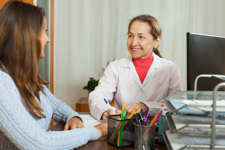 malaise: Sick young woman complaining  to doctor about symptoms of malaise Stock Photo