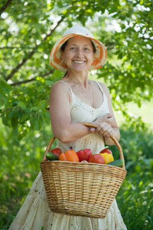 mature woman with basket of harvested vegetables photo