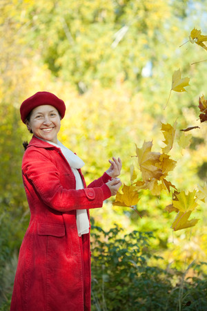 Happy mature woman throwing yellow maple leaves in the air in autumn  Stock Photo - 29982166