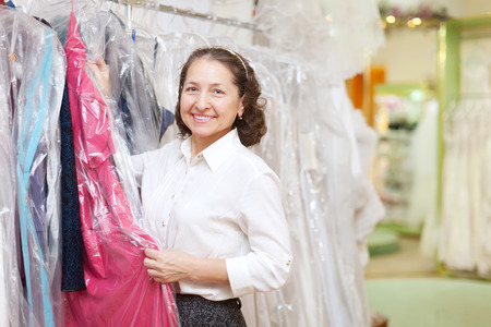 Happy mature woman  chooses dinner gown at boutique photo