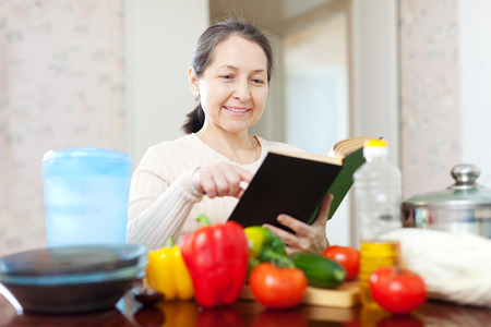 mature woman cooking with cookbook in the kitchen Stock Photo - 29982168