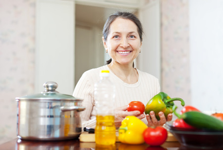 Happy mature woman cooking veggie lunch with vegetables  Stock Photo - 29982169