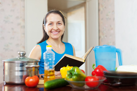 mature  woman reads cookbook in the kitchen at home Stock Photo - 29982170