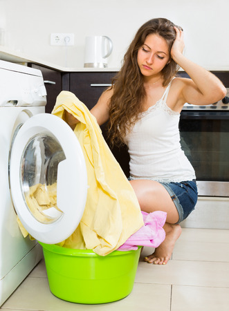 Home laundry. Tired girl with clothes near washing machine at home photo