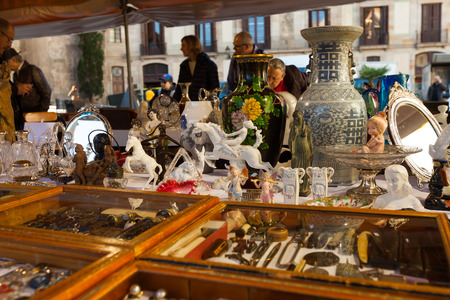 jumble: BARCELONA, SPAIN - FEBRUARY 20, 2014: Counter with old  things at flea market at square before Barcelona Cathedral