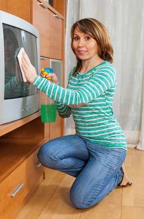 televisor: Handsome housewife in green cleaning TV with rag at home Stock Photo