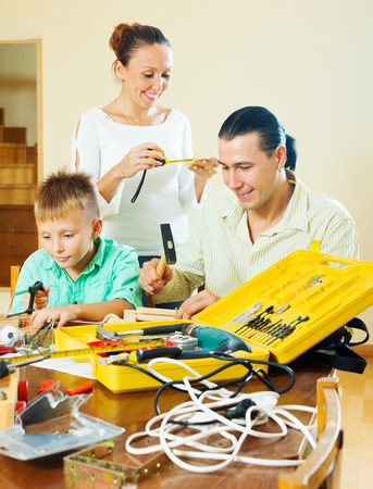 family of three with teenage boy doing something with the working tools photo