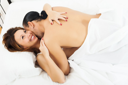 adult sex: Happy adult couple having sex on white sheet in bed   Stock Photo