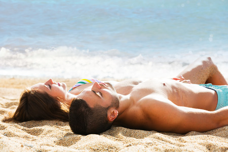 Young couple laying on sandy beach at sea shore in sunny day photo