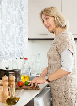 spliting: Mature housewife spliting veggy lunch in kitchen