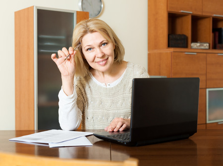 utility payments: Smiling mature woman fills in the questionnaire in laptop  at home interior Stock Photo