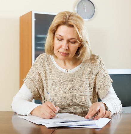 serious mature woman with financial documents at  interior photo