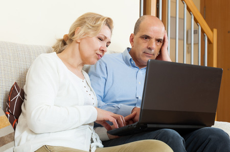wistful: Wistful mature couple  with laptop in room at home