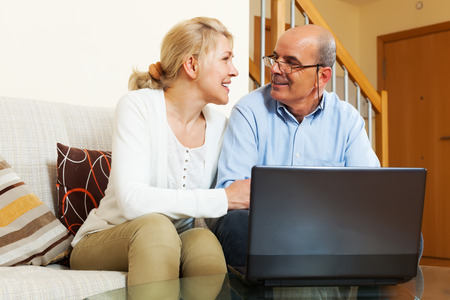 Mature couple with notebook at table at home photo