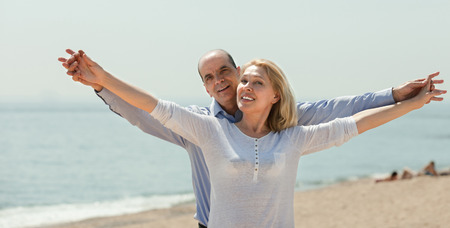 Happy elderly couple holding hands on the beach photo